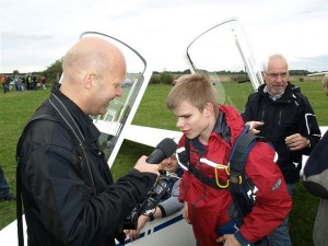 Nach dem Flug: Emanuel Ernst im Interview mit Jo Schrader. Weiter im Bild: Pilot Martin Plass und Segelflieger Fritz Hornbach